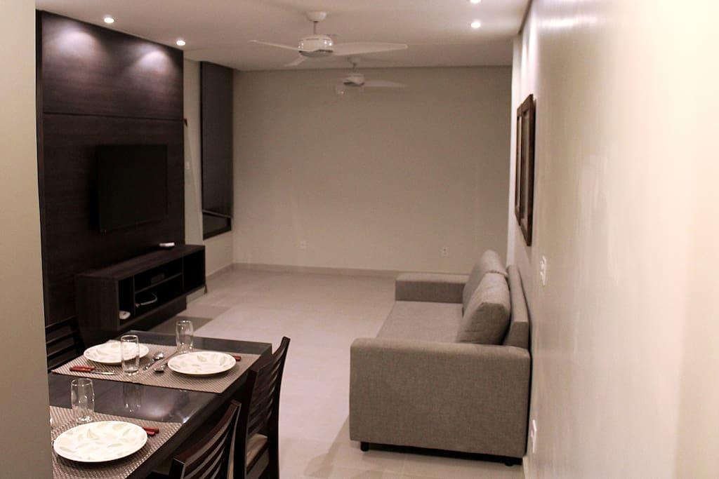 sala de estar com sofá, tv a cabo e 2 ventiladores de teto