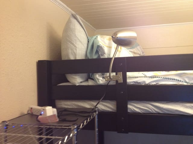 Top of the free standing closet is available as a night stand. Clip lamp on bed.