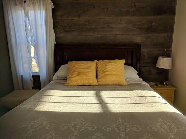 Queen-size bed in an open floor plan on the main floor