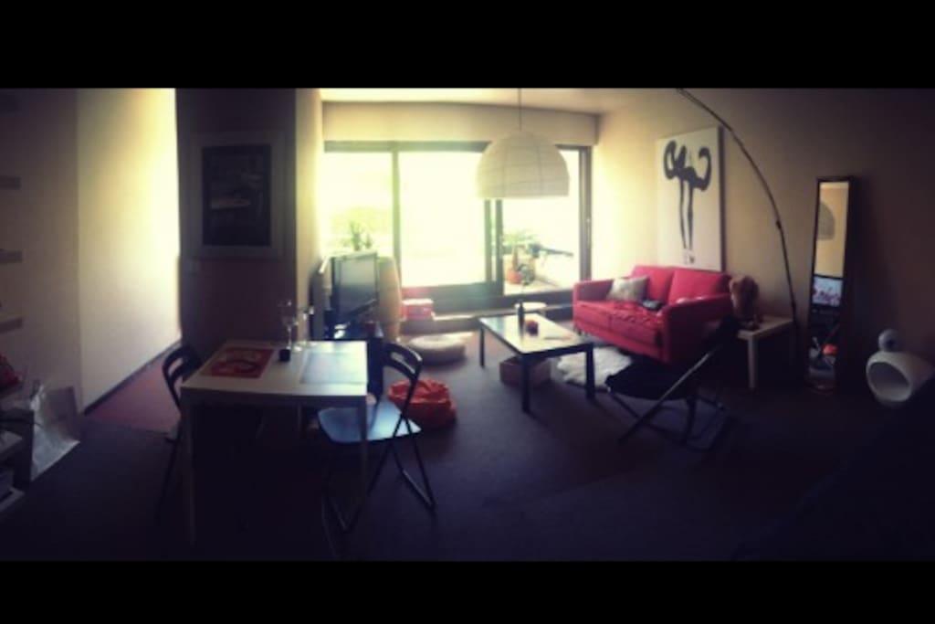 Grande pièce à vivre, avec baies vitrées tout du long et lit + salle de bain à droite