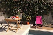 Vue piscine avec grande terrasse en pierre naturelle