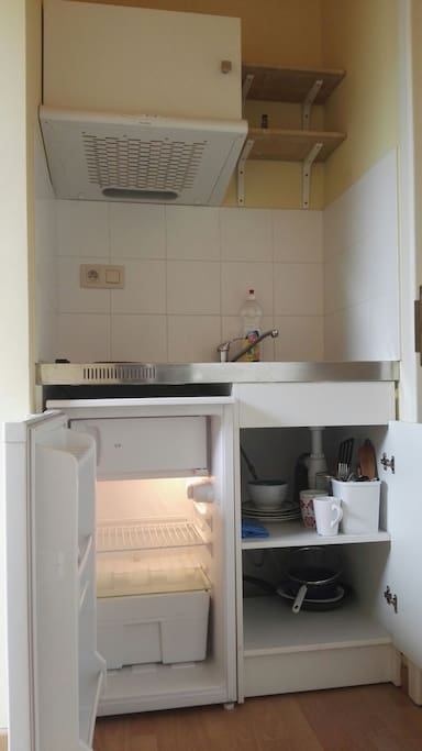 Kitchenette with plates and cutlery, coffee maker etc.