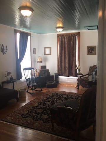 "The living room known as ""JJ's room"" has original wood flooring, doors and windows from 1850. The ceiling paint was matched to the original color. This room faces S. Crockett St where the stagecoaches would have arrived from 1847-1874."