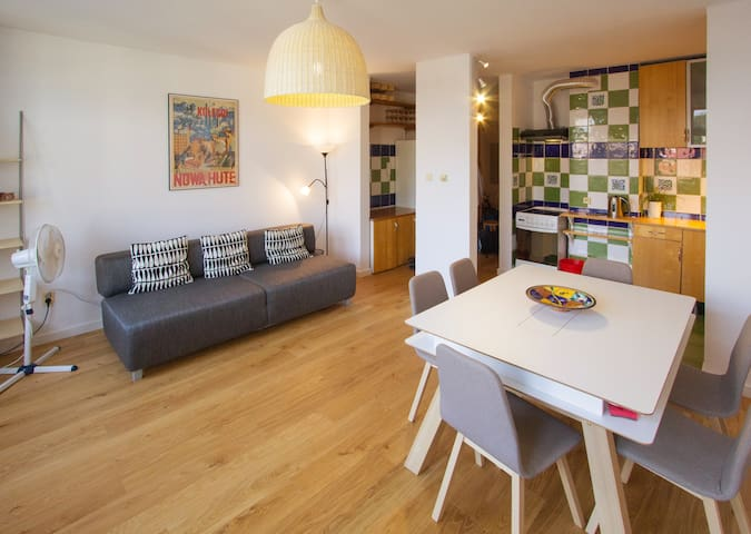 Living and dining areas with natural made of wood floor. The sofa can also be used as a third double bed for 2 guests on the 4th level of the flat.