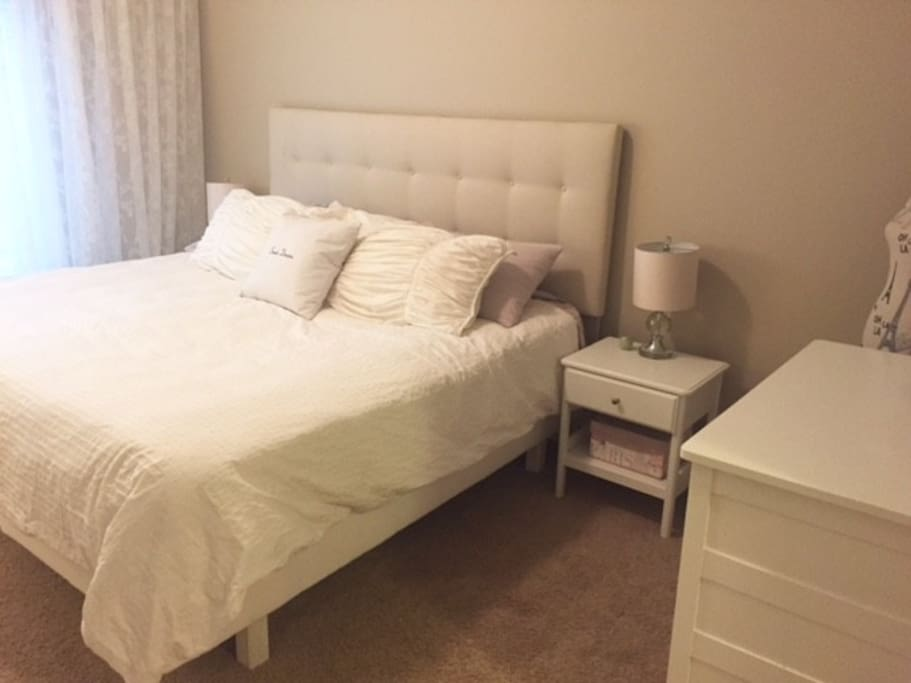 Spacious bedroom with king sized bed and view of Griffith Woods