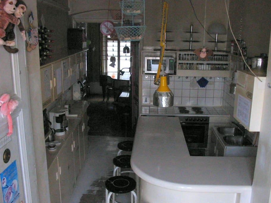 kitchen (RIN 109), in background dining/living/music room (RIN 104) with baby grand piano