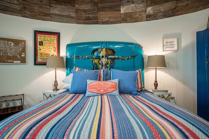 Queen bed with custom painted headboard painted by the owner - an old truck hood!  The owner's brother loved that truck & when he wrecked it, he gave Bonnie the hood and it lives on, large & in charge with a forever Texas icon, upstairs in the loft