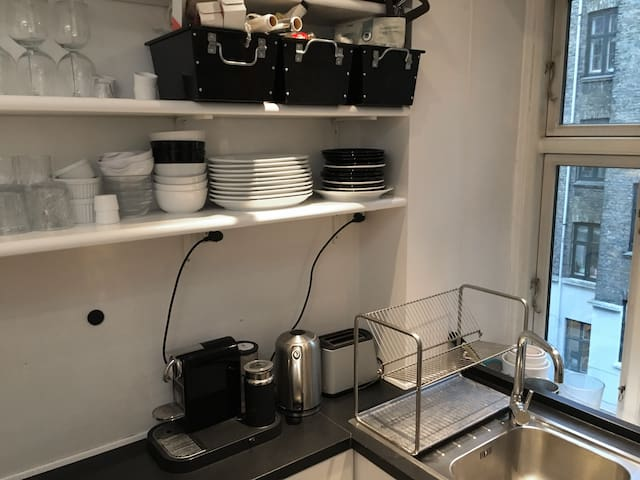 Plates, glases for all purposes, coffee machine nespresso, water boiler, sink and a view to the yard. We also have spices in the boxes