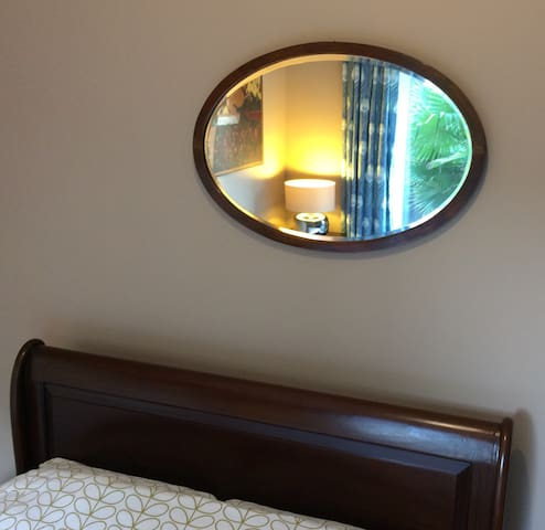 Double (4'6) low end mahogany sleigh bed in guest bedroom