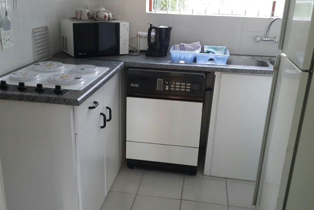 Kitchen with washing machine, microwave, 4 plate hob, fridge.