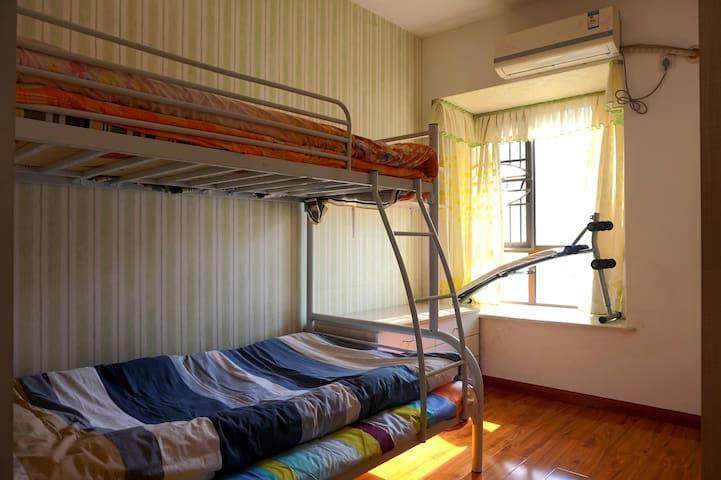 这间卧室里有上下双层床,到顶大衣柜、空调。
