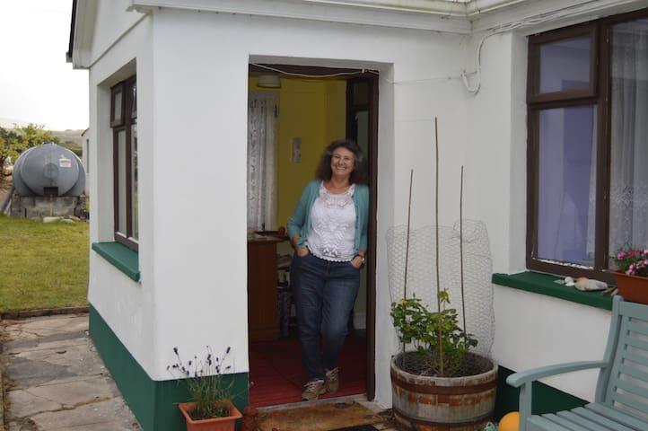 Jane, welcoming you in the porch doorway.