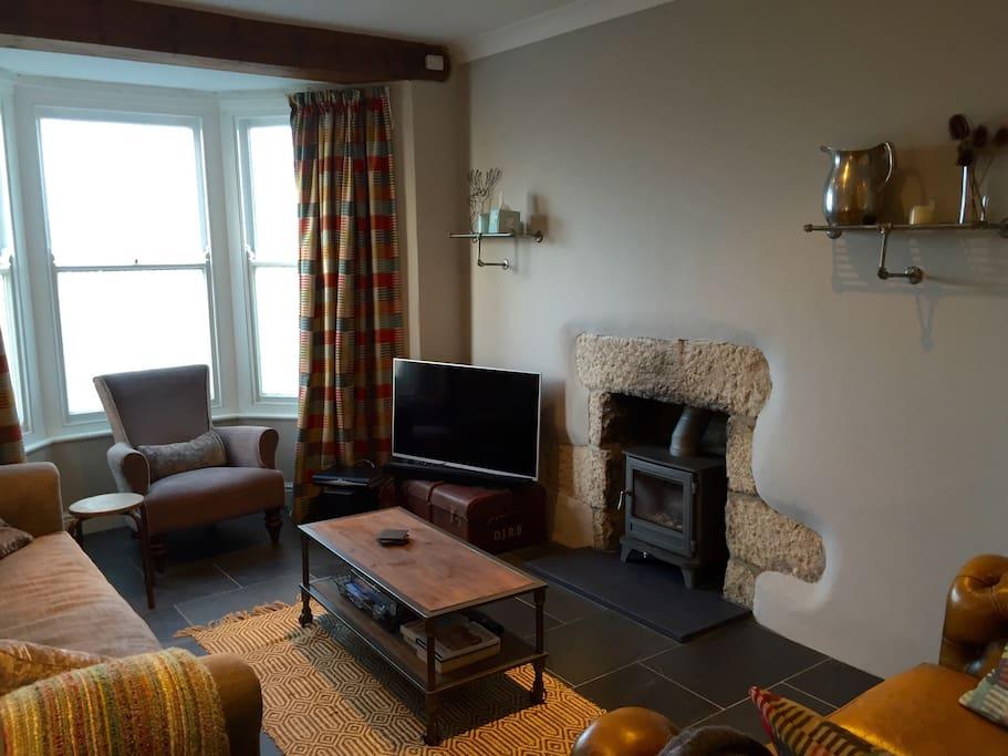 Spacious living space with log burner.
