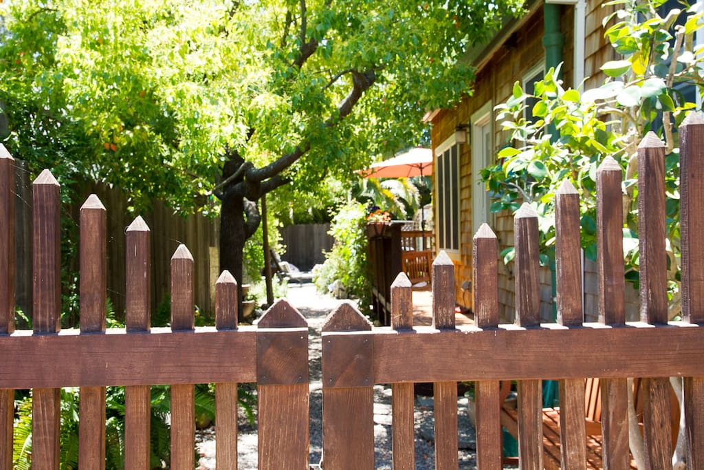 Park on cobblestone driveway and walk past wooden gate.