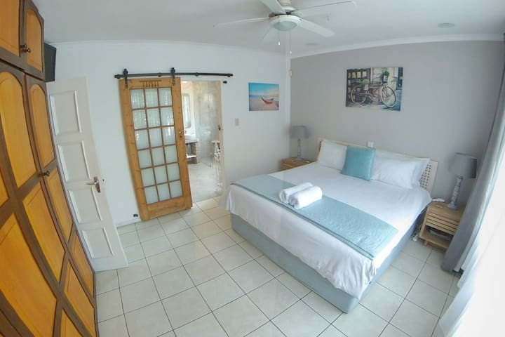 Main En-suite with King size bed, TV, heated flooring, double basin vanity, corner bath, large walk-in shower and an open walk-in closet with polished concrete finish.