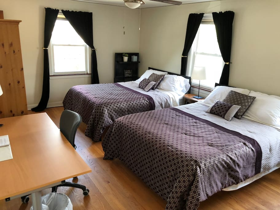 Largest bedroom with two queen beds, two closets, and a desk.