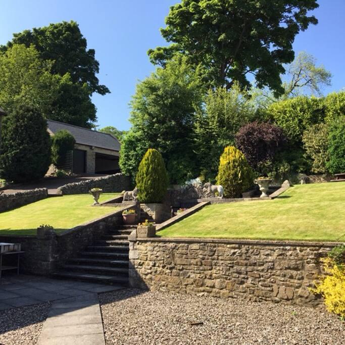Gardens with garage beyond