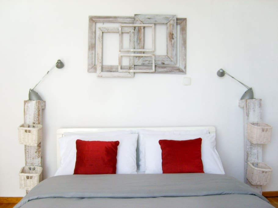 The double bed with the artsy bedside stands and the artwork above