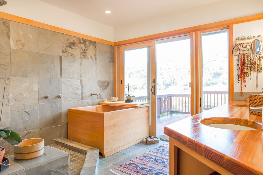Master bath includes an open shower, soaking tub and view of the lake and hillsides.
