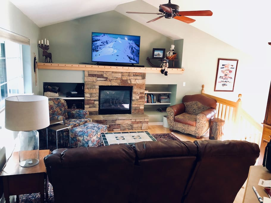 "Sunny living room with large windows, vaulted ceilings and great views.  55"" TV over the gas fireplace has cable, DVD player, and internet connected apps (Netflix, Amazon, YouTube, etc.).  Not pictured: new large L-shaped leather sectional that fits 8 people."