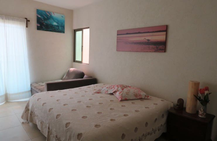 Recámara principal con cama king size y sofá, climatizada