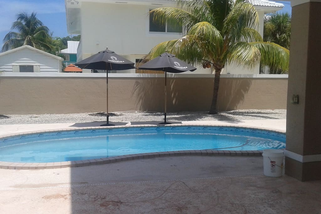 Pool down stairs in breezeway area equipped with table, hammock, lounge chairs and tv