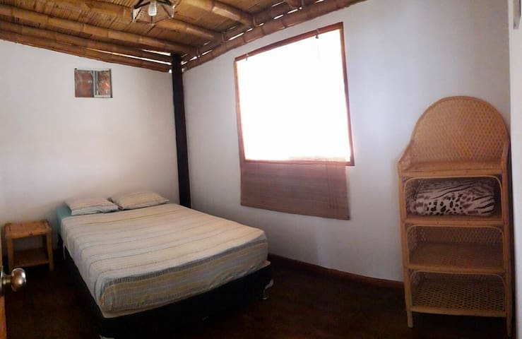 Habitación Matrimonial, cuenta con cama de dos plazas, velador y estante organizador para ropa u otros artículos personales.