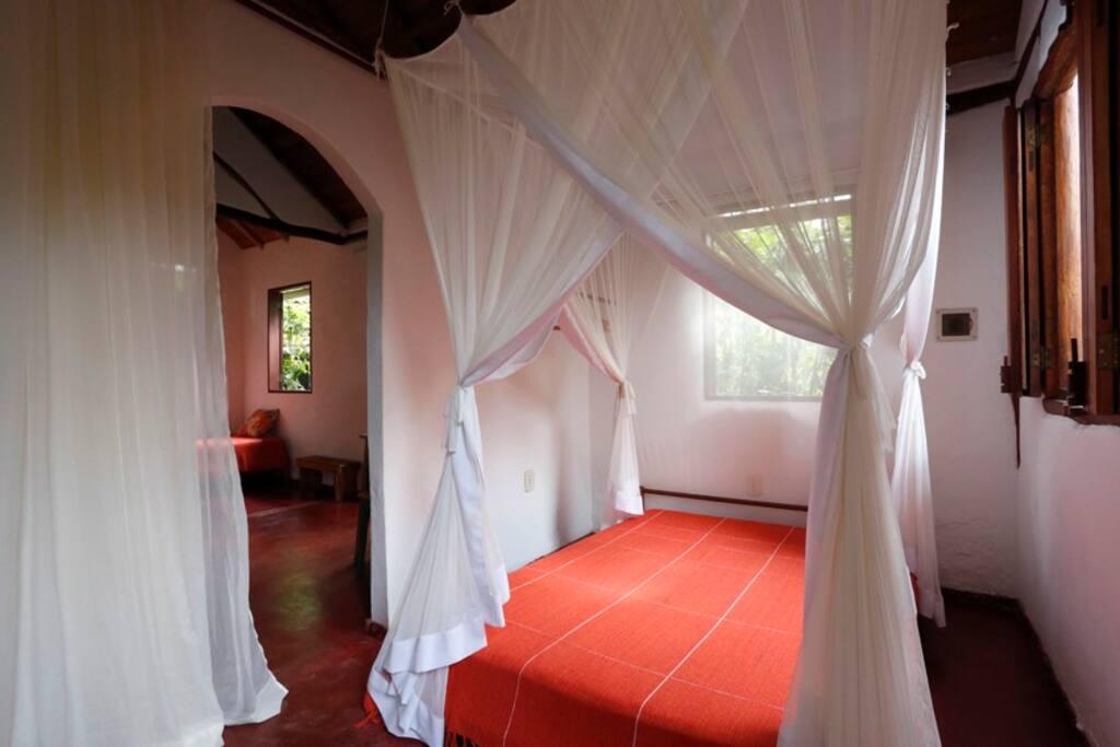 O primeiro cômodo tem duas janelas, cama de casal, um gaveteiro e prateleiras