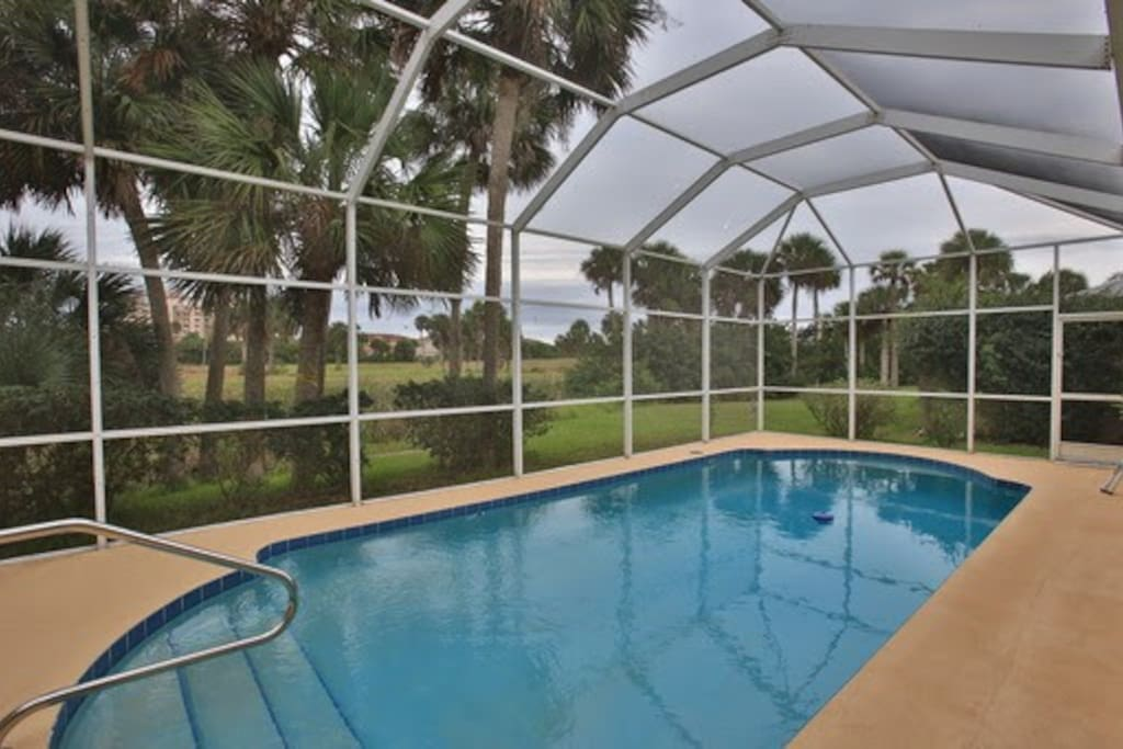 Private, screened in pool with view of the golf course and pond.