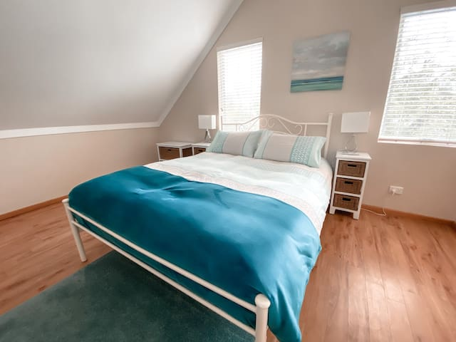 Upstairs Queen bed, bedside table, lamps, duvet, pillows & linen. Ensuite with shower over spa bath. Separate toilet.