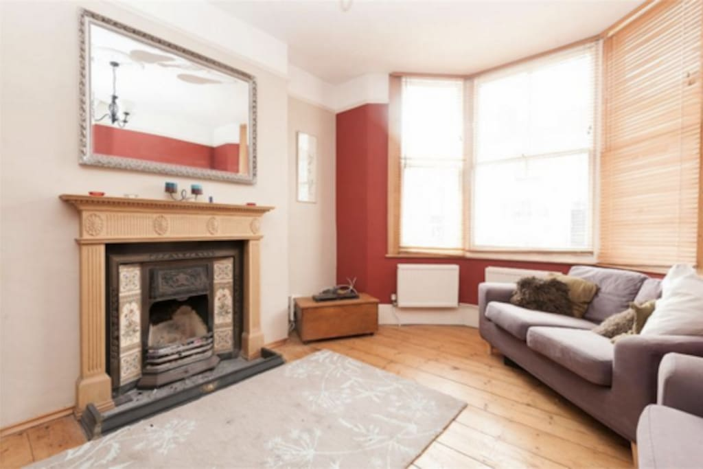 Bright and cozy living room with working fireplace, upright piano and a selection of games
