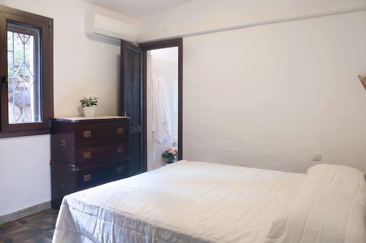 Camera da letto con bagno privato e vista giardino. Bedroom with private bath and garden view.