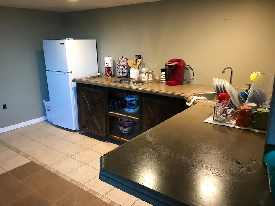 Kitchenette. Outfitted with a Keurig coffee machine, small refrigerator, small cooktop and a small sink. Also has a regular sized toaster oven and dishes for your use. Please wash dishes if you use them. Please and a Thank You!