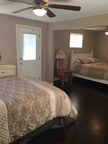 Extra large bedroom with door that opens up to back yard.  There is a queen and a full size bed in this room.  Additionally there are 2 kid toddler bed cots like they use in a daycare in closet if needed.
