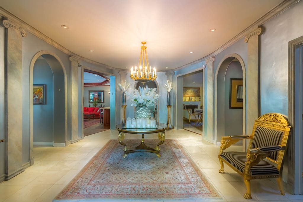 The marble and limestone entry foyer features a large chandelier.