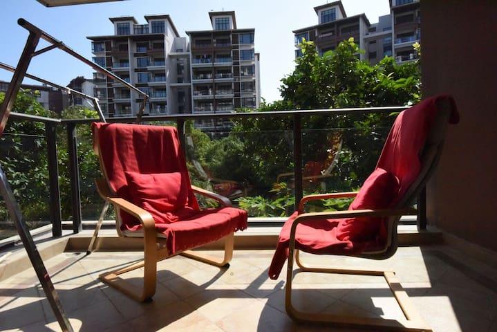 阳台前一棵菩提树,一对红色躺椅,触手可及楼下木瓜,喜欢一家人安静度假的你,一个温暖的家就在这里,等你