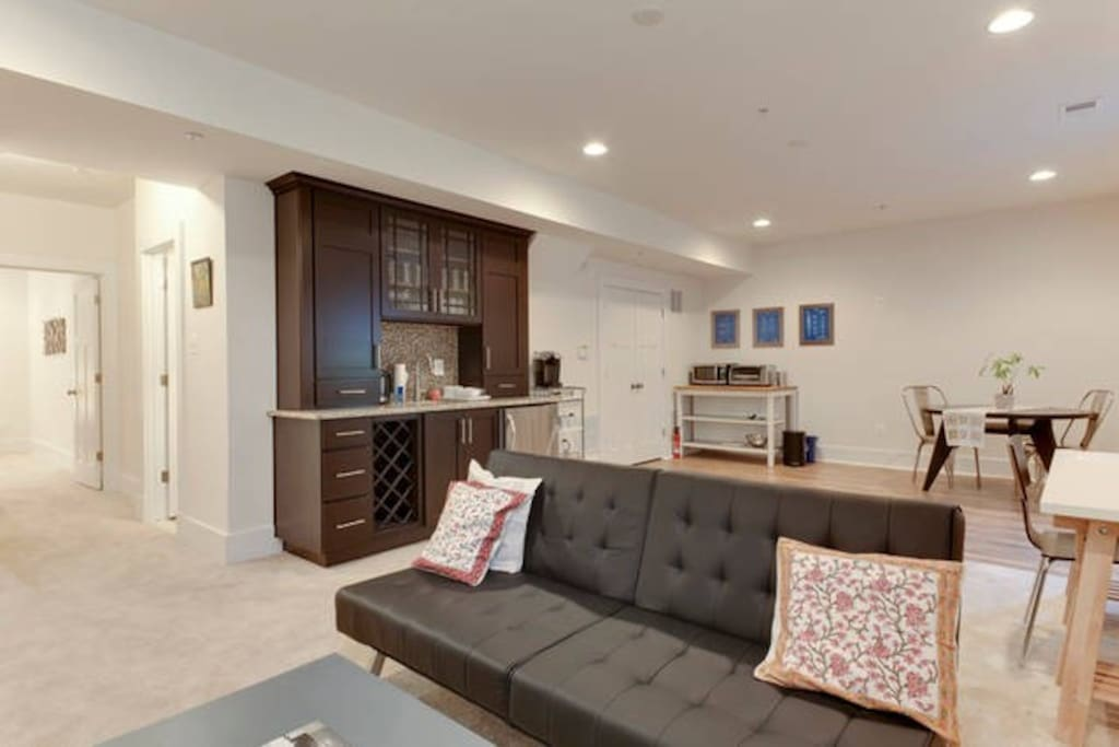 Spacious main room with wet bar, kitchenette, dining table, work desk, and futon that folds into a bed