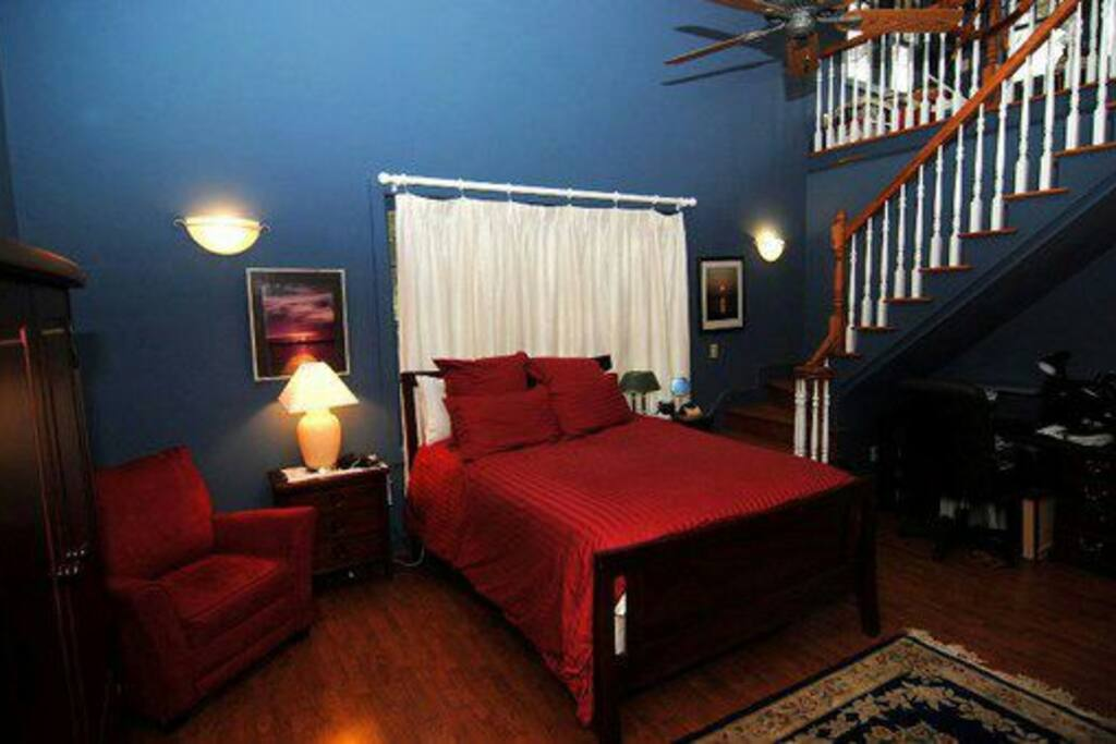 Master Bedroom and stairway to quiet loft to study, read or use as your little get away, tucked in the tree tops.