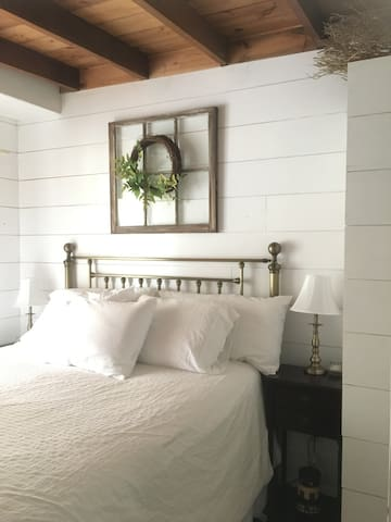 Your room has a ceiling from the early 1900s that sits high above a comfy queen bed