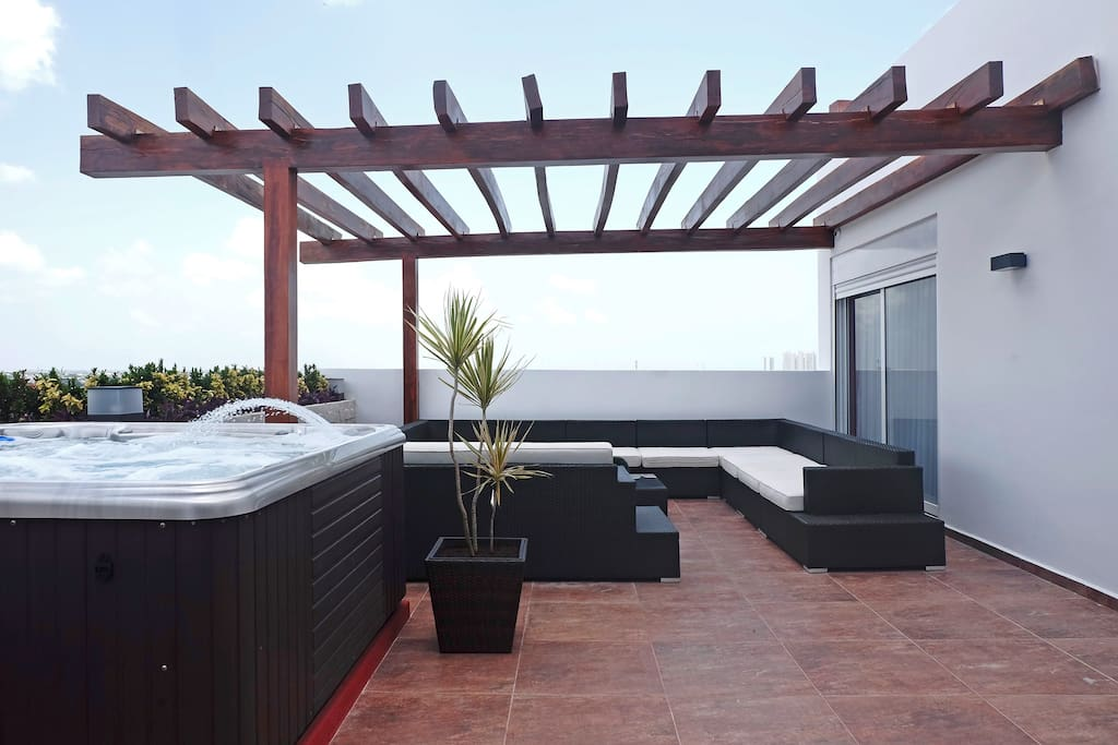 Large terrace with plenty of seating and a hot tub.