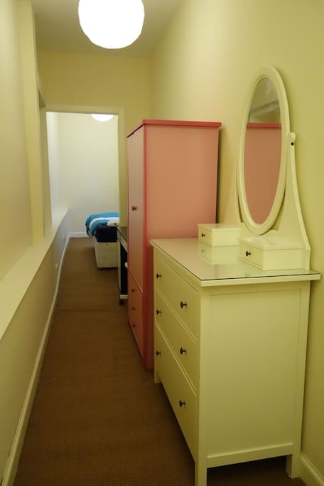 Large dressing table with mirror, desk and wardrobe in bedroom.