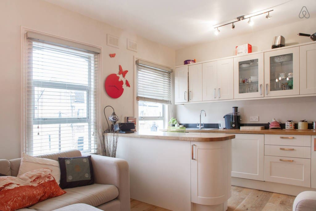 Open plan lounge and kitchen with bar stools to have breakfast at
