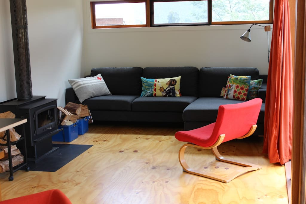 Comfy couch and wood heater in living area.
