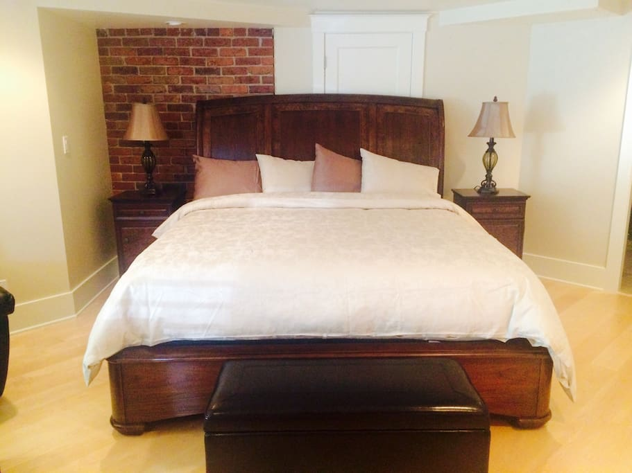 King bed with luxurious linens, exposed brick feature wall
