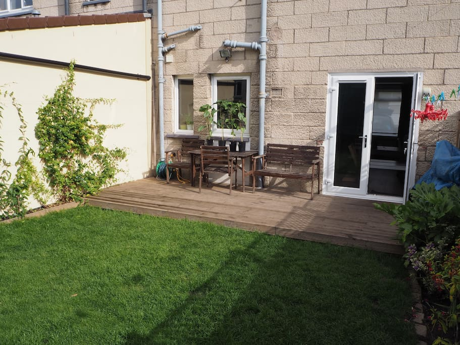 Double patio doors lead from the open plan living room/kitchen out to the enclosed garden.