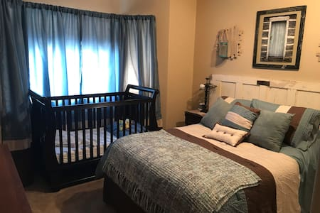 Full size bed with crib in room