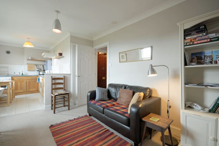 There is a small open plan sitting room with a two seater sofa, club chair and coffee table. There is wifi and a 'Smart' TV and DVD player. There is some local information in the bookcase.