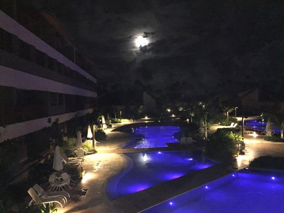 Vista noturna das piscina na frente do apartamento.