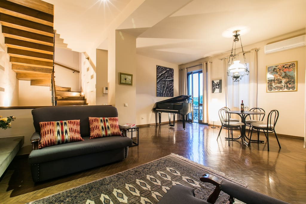 Spacious living room with sofa, arm-chair, table for 4 and piano for music lovers
