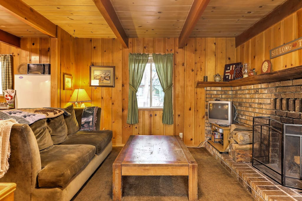 The rustic cabin features wood walls, ceilings and furniture throughout the interior.